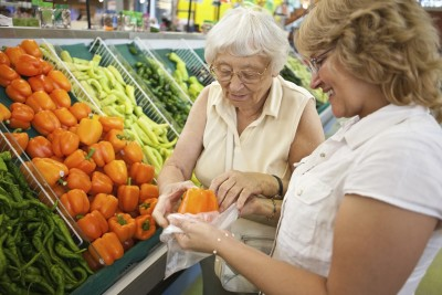 Home care caregiver helping senior with her shopping_s